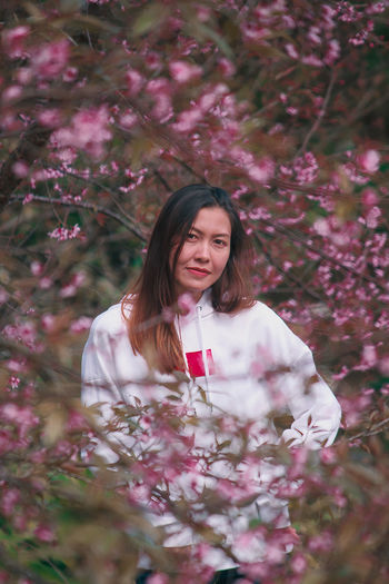 Portrait of beautiful woman standing by pink flower tree