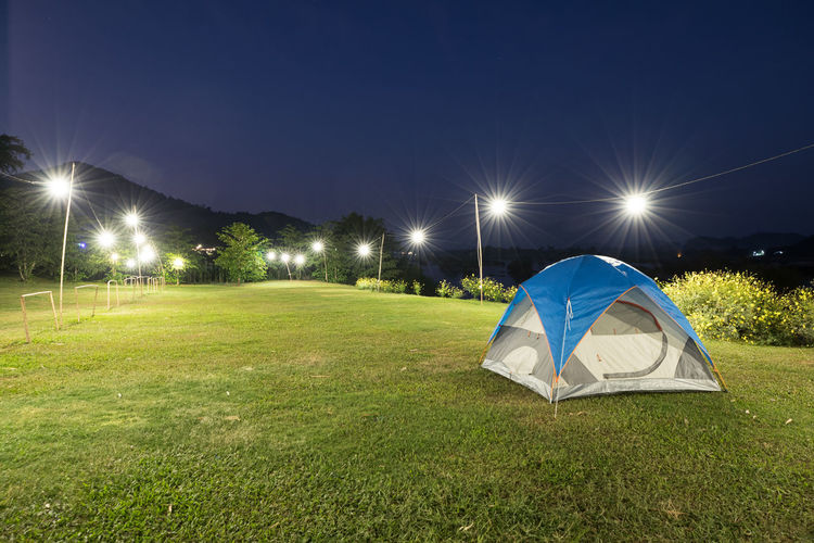 Illuminated tent on field against sky at night