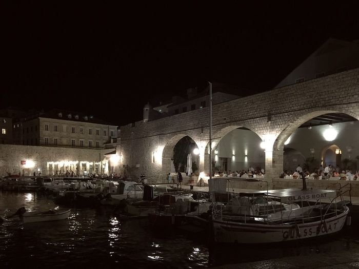 Dubrovnik old harbor by night in Croatia Light Arch Architecture Building Exterior Built Structure City Dubrovnik Illuminated Nautical Vessel Night Old Harbor Old Port Outdoors Real People Reflection Sky Travel Destinations Water