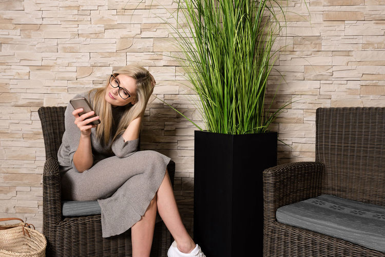 Young woman using phone while sitting on chair in waiting room