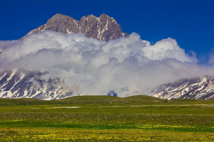 Photo of Gran Sasso peak in Abruzzo Italy Abruzzo Cloud Flowering Gran Sasso D'Italia High Trekking Apennines Beauty In Nature Campo Imperatore Cloud - Sky Environment Europe Fog Gran Sasso Idyllic Italy Landscape Meadow Mountain Mountain Range Non-urban Scene Peak Scenics - Nature Summer Wild Flowers