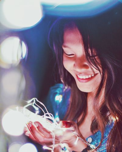 Close-Up Of Happy Young Woman With Illuminated String Light