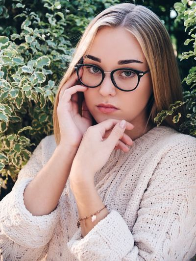 Portrait Of Young Woman Wearing Eyeglasses Amidst Plants