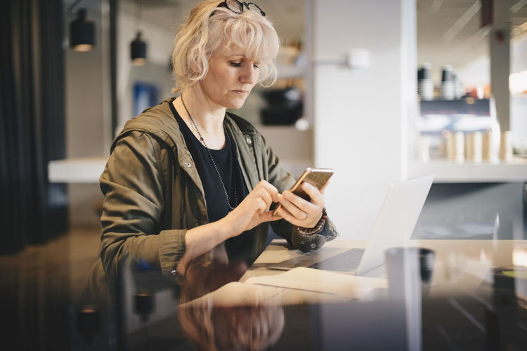 Mid adult woman using mobile phone