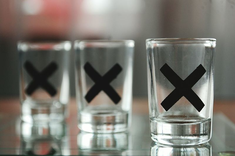 Close-Up Of Cross Shape On Empty Shot Glasses At Table