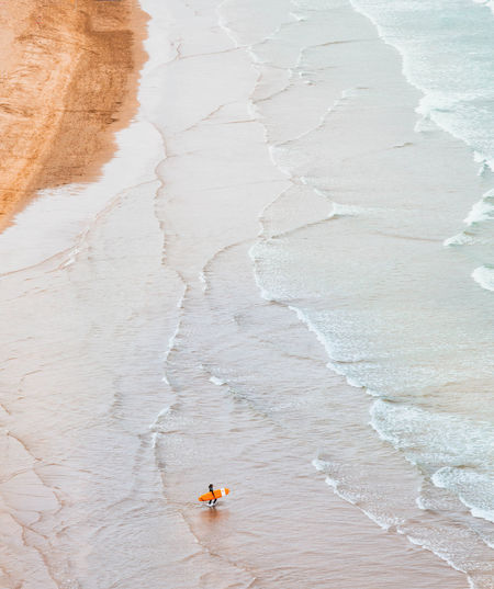 Aerial view of mature man with surfboard at beach