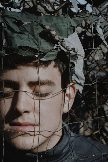 Close-Up Of Young Man With Eyes Closed Behind Nets