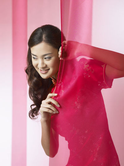 young chinese woman with red curtain Gong Xi Fa Cai Greeting Happiness Adults Only Beautiful Woman Chengsam Chinese Ethnicity Chinese New Year Color Background Day Front View Holding Indoors  Leisure Activity One Person One Woman Only One Young Woman Only Pink Color Qipao Red Curtain Smile Smiling Standing Young Adult Young Women