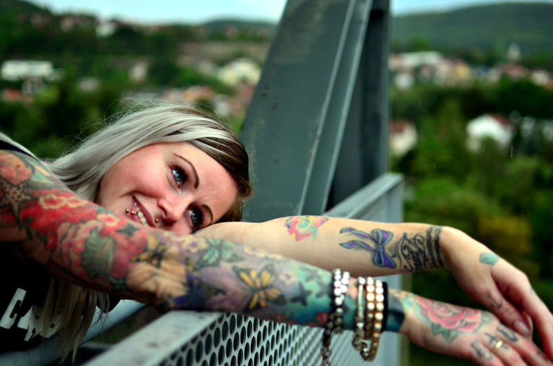 Smiling Young Woman With Tattoo On Hands Leaning On Metallic Railing