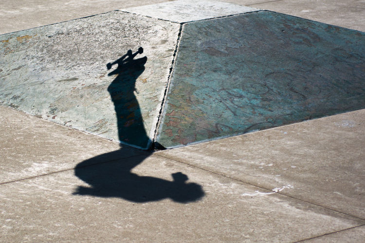 Low section of man with shadow on concrete