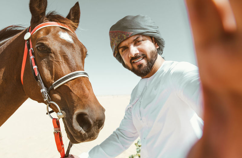 Portrait of man taking selfie with horse