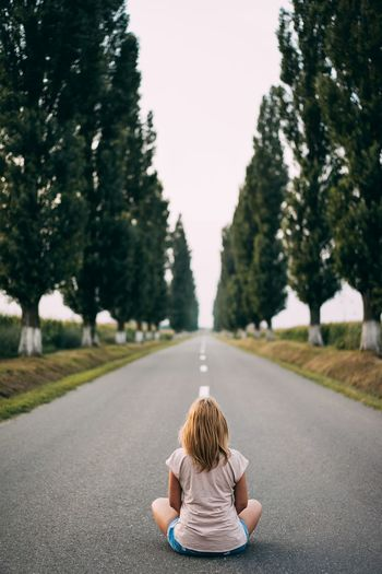 Rear View Of Girl Sitting On Road