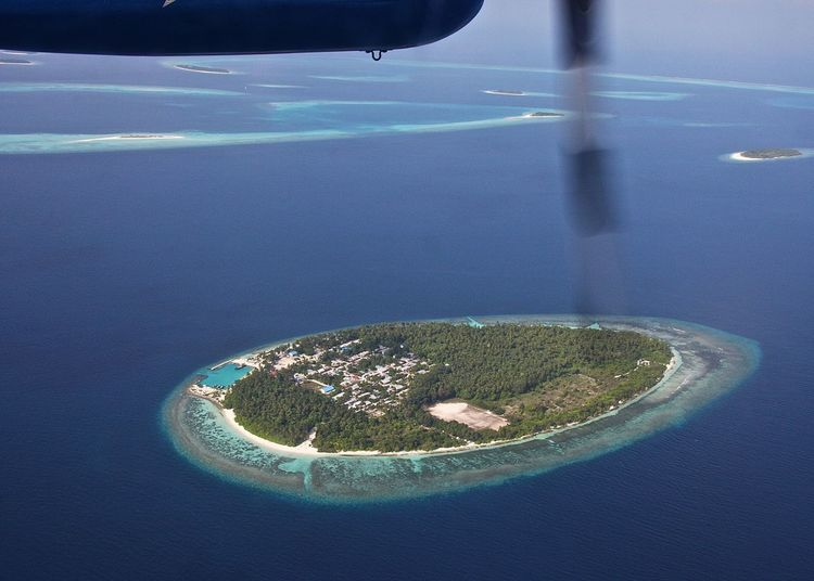 Cropped image of airplane flying over atoll in sea