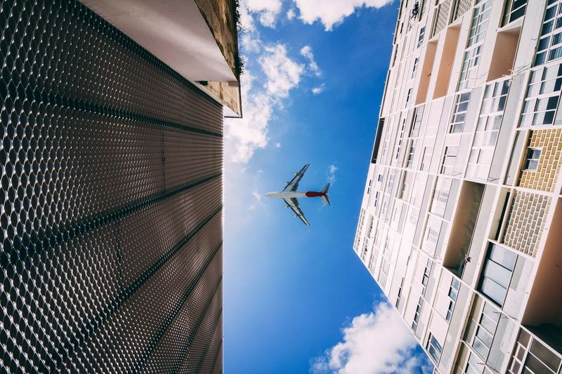 Directly below shot of buildings and airplane flying in sky