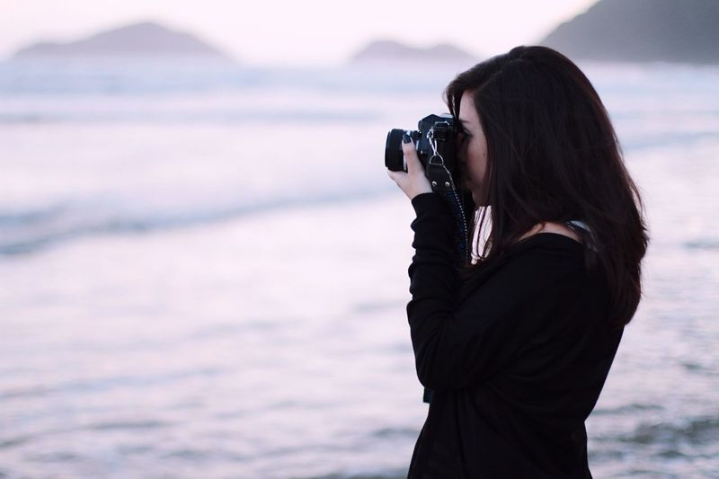 Side view of woman photographing from slr camera against sea