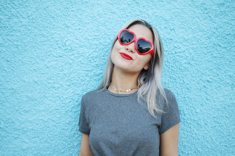 Glasses Sunglasses One Person Fashion Hair Women Blue Leisure Activity Wall - Building Feature Lifestyles Real People Portrait Casual Clothing Front View Waist Up Hairstyle Young Women Child Beautiful Woman Heart Red