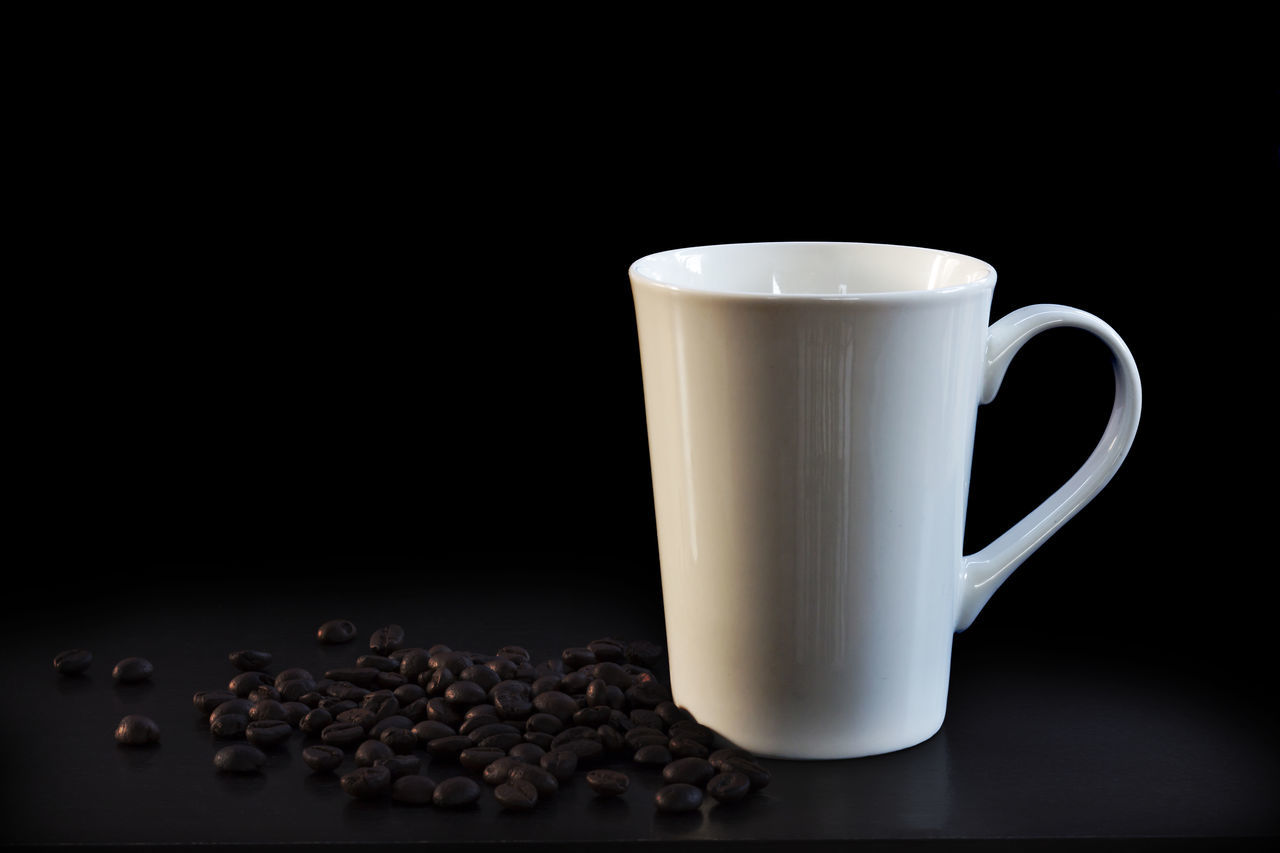 Close-Up Of Coffee Cup With Beans On Table Against Black Background