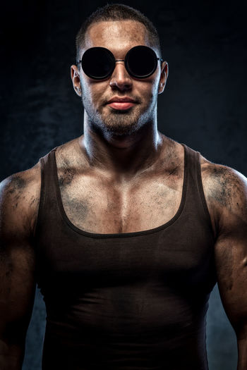 Portrait of confident muscular worker wearing sunglasses