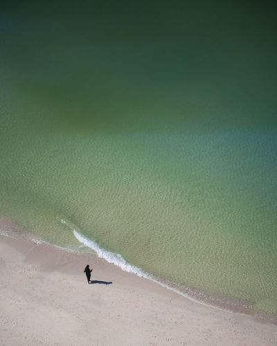 Person on beach by sea