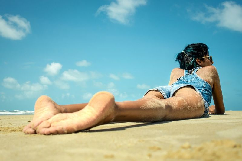 Rear View Of Sensuous Young Woman Lying On Sandy Beach Against Sky