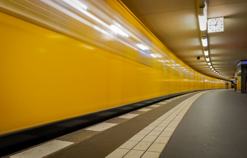 Blurred motion of yellow train at railroad station