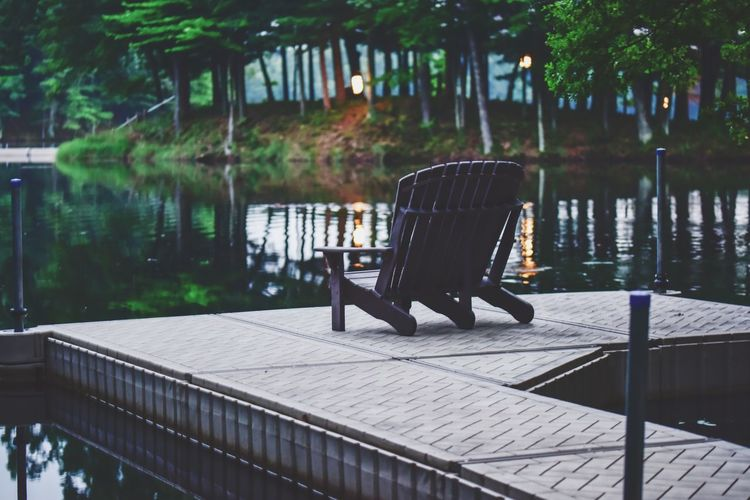Empty chairs by lake in park