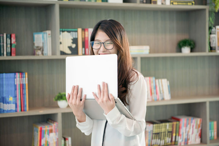 Business Asian woman holding a laptop in library Asian  Office Adult Book Bookshelf Business Business Woman Computer Corporate Business Day Education Eyeglasses  Focus On Foreground Front View Holding Indoors  Laptop Library Lifestyles Meeting Room Occupation One Person People Reading Glasses Real People Shelf Student Women Working Young Adult Young Women