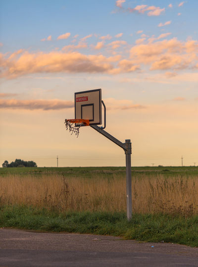 Basketball hoop on field against sky during sunset