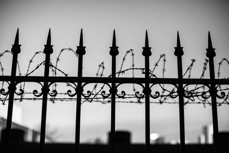 Low angle view of silhouette fence against sky