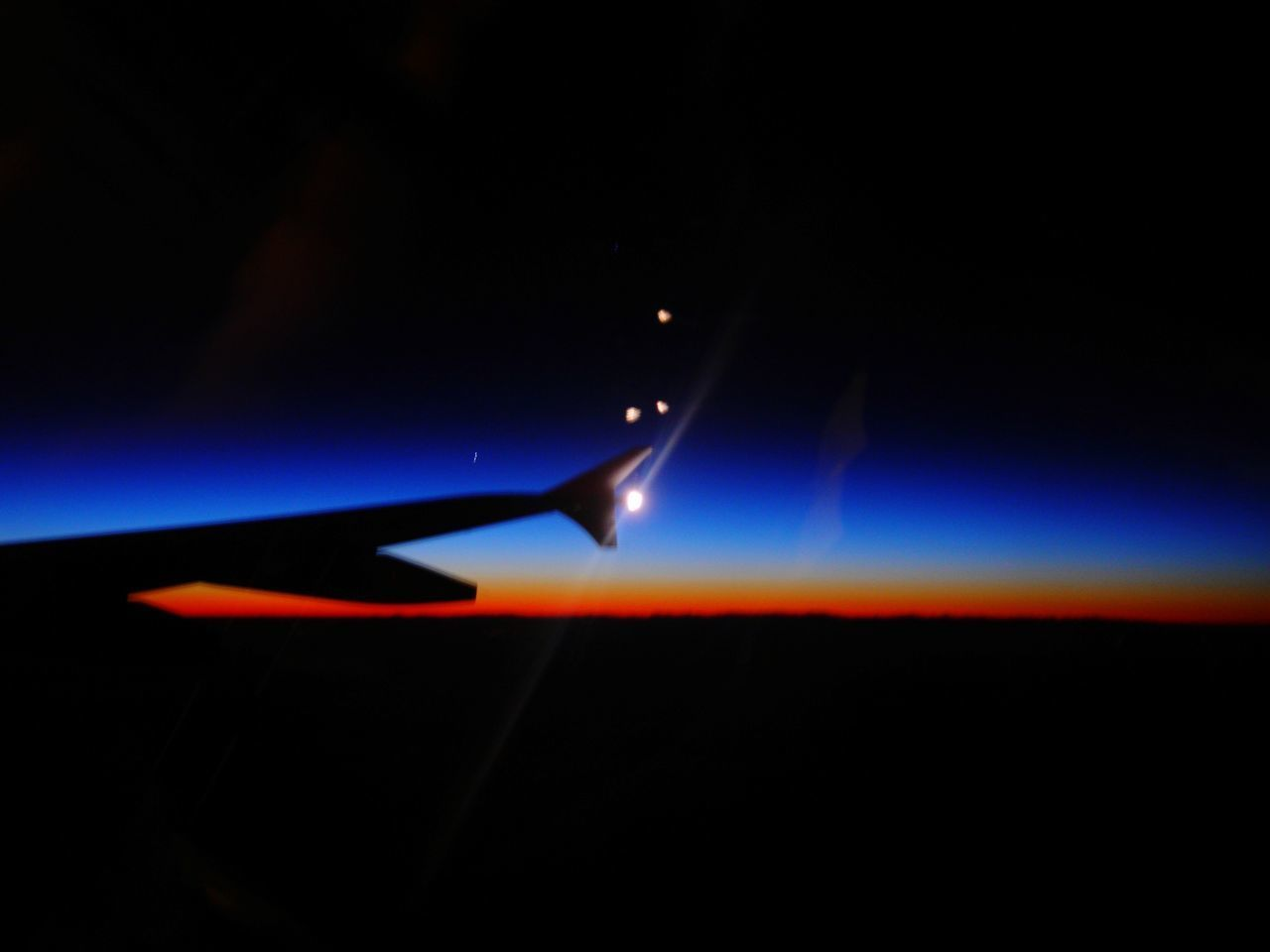 airplane, air vehicle, night, no people, sky, mode of transportation, flying, illuminated, nature, transportation, travel, motion, mid-air, dark, aircraft wing, outdoors, silhouette, vehicle interior, beauty in nature, copy space, aerospace industry, nightlife