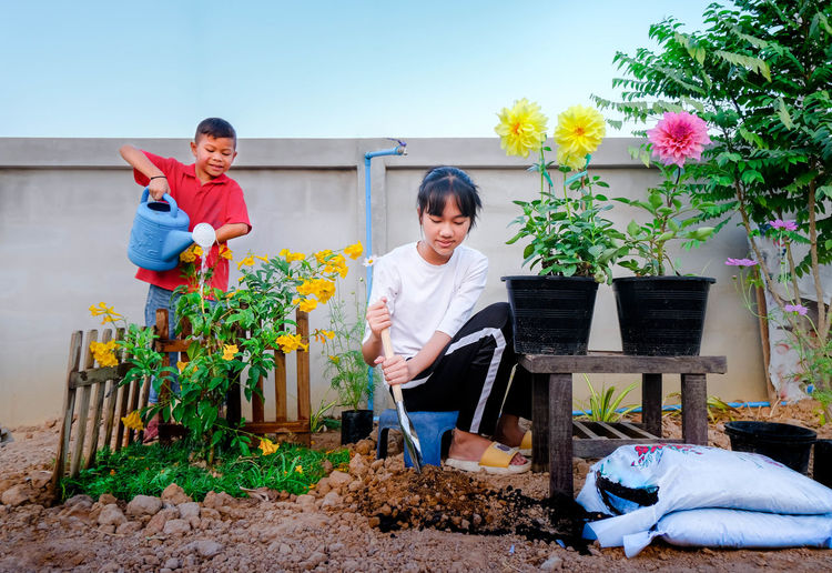 Full length of father and son on flower plants
