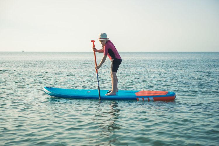 Girl paddleboarding on sea against clear sky