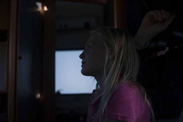 Girl looking away against window in motor home