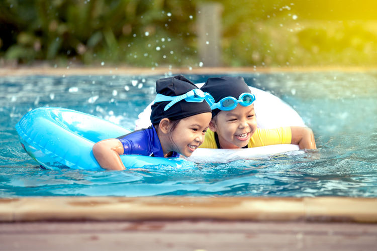 Happy sisters with inflatable rings swimming in pool