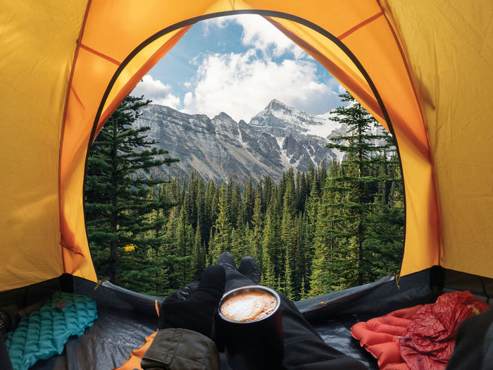 Traveler lying and holding coffee cup in yellow tent and enjoy the view of forest and mountain