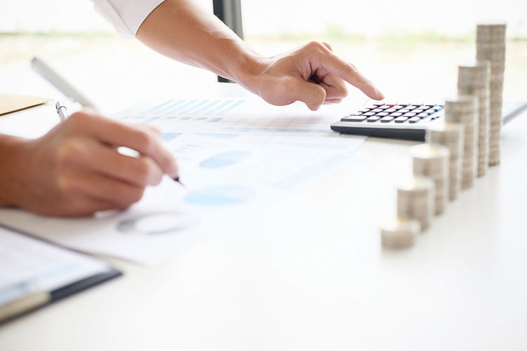 Close-up of business person counting coins in office