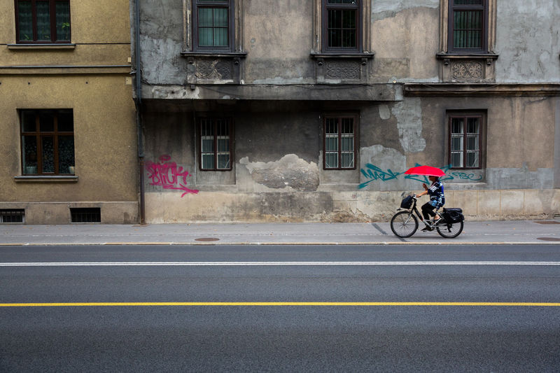 Transportation Architecture Building Exterior City Mode Of Transportation Built Structure Road Building Street Side View Full Length One Person Window Day Bicycle Land Vehicle Outdoors on the move Riding Old Buildings Umbrella Lines Copyspace Single Bicycle Driver Old Town
