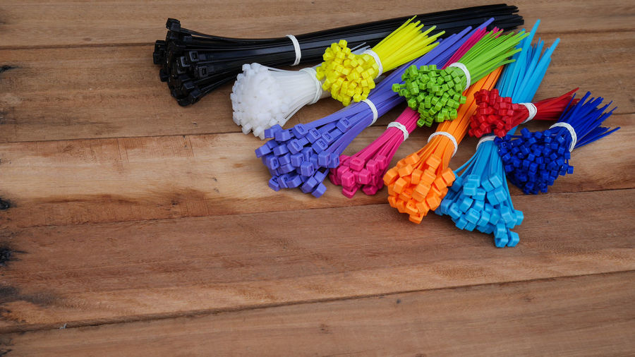 Self-locking plastic tying cables on wooden background and close-up colorful cable ties selective focus. Attach Background Band Belts Blue Bunch Bundle Cable Close-up Colorful Electrical Fastener Green Heap Lock Material Nylon Plastic Red Strap Tie Tool Wire Wood Zip