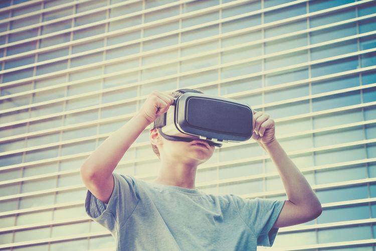 Boy wearing virtual reality simulator against building