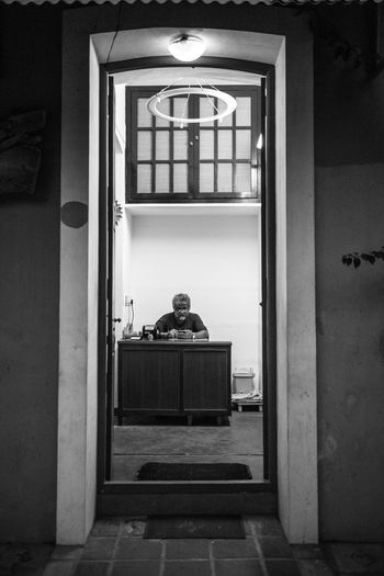 Killing time Walking through the old neighbourhood of old 'Pondi', I noticed this doorway and the desk at the end of it. The man behind the desk never noticed me as I took my time to photograph him. He was too busy, killing time. Adult Adults Only Browsing Communication Doorway Indoors  Internet Night Office One Man Only One Person Only Men People Perspective Phone Real People Reception Hall Street Black And White Mobile Conversations