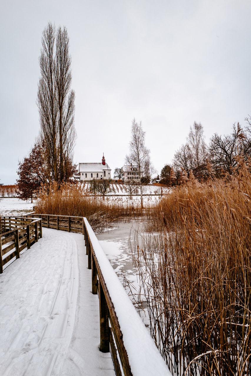 Snow Covered Footbridge Over Frozen Lake Against White Sky
