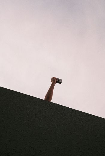 Low angle view of person against wall