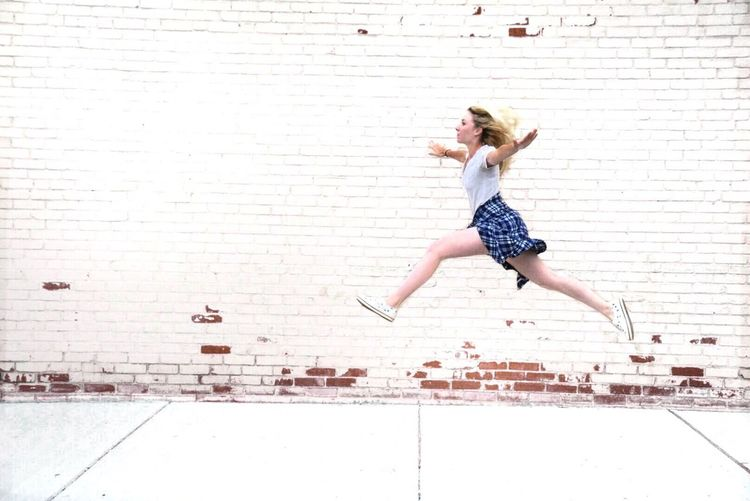 Full Length Of Woman Levitating On Sidewalk Against Brick Wall