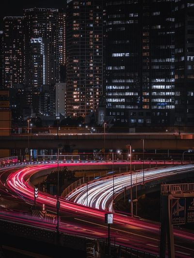 Light trails on road against illuminated buildings at night