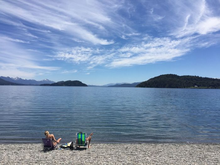 Beach Beauty In Nature Cloud - Sky Couple - Relationship Day Lake Leisure Activity Looking At View Men Mountain Nature Non-urban Scene Outdoors Real People Scenics - Nature Sitting Sky Tranquil Scene Tranquility Two People Water Women