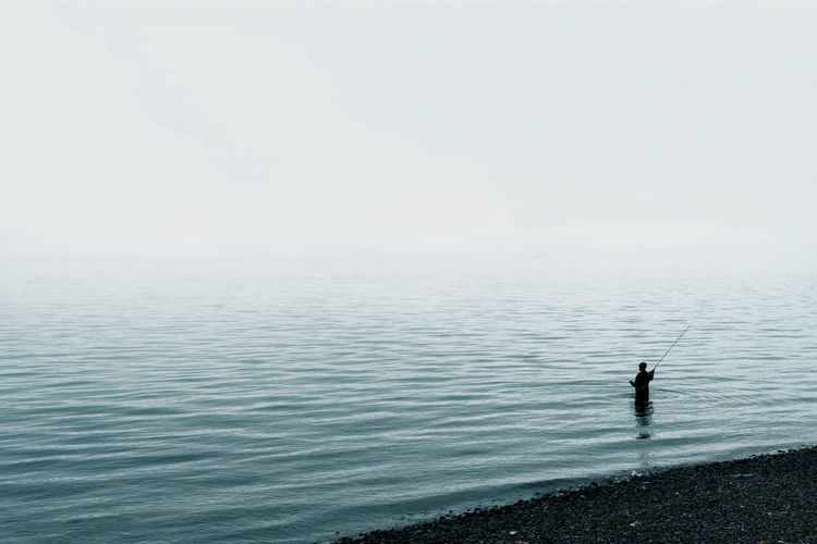 Fisherman casting fly line off shore with dense fog over water.