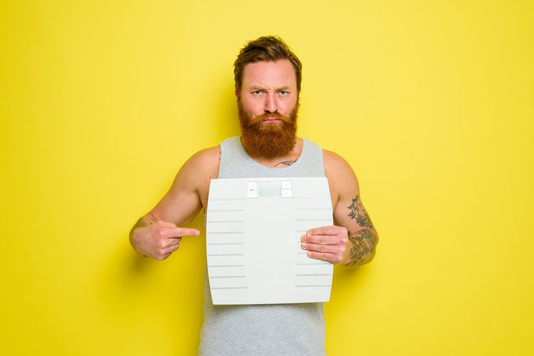 Portrait of man against yellow background