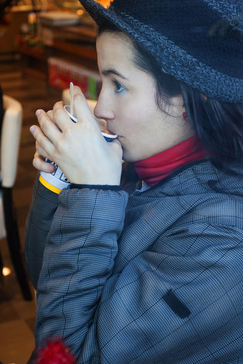 Close-up Young woman in a coffee shop drinking One Person Clothing Leisure Activity Holding Lifestyles Real People Hat Looking Away Portrait Young Adult Food And Drink Focus On Foreground Looking Adult Waist Up Day Drink Headshot Side View Drinking Warm Clothing Woman Cafe Coffee Breakfast Young Women Young Coffee Cup