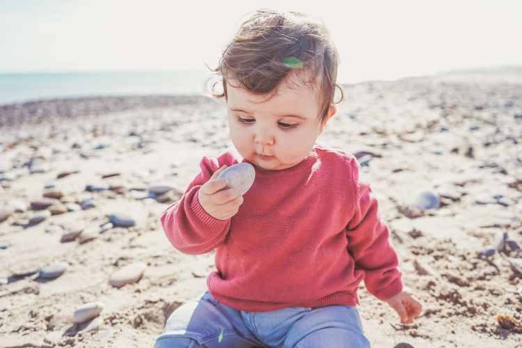 Cute girl holding pebble stone on beach