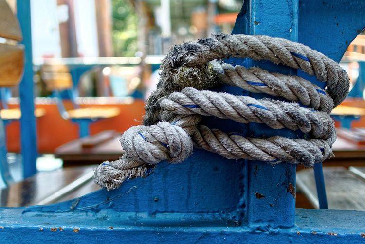 Close-up of rope tied on blue metal post
